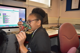 Girl showing a Codebug wearable controller in front of her face
