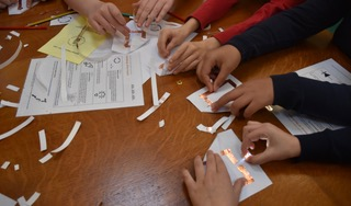 4 pairs of hands creating paper circuits