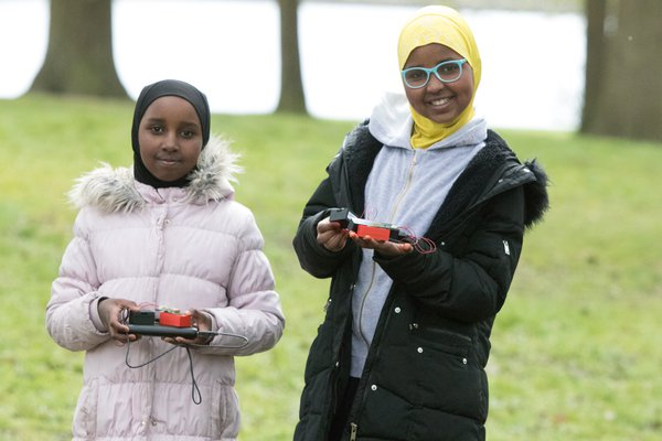 girls pleased with their air quality sensor in trees