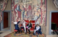4 girls sat on a chair in front of a tapestry in a room at bolsover castle