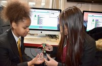 2 girls working with Codebug device in front of a computer